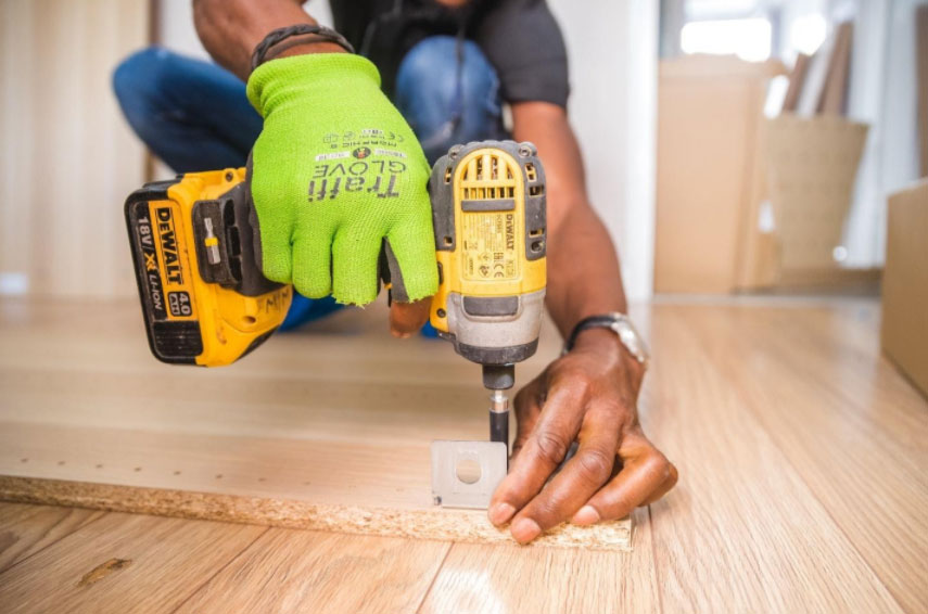 A general contractor drilling holes into a wood plank
