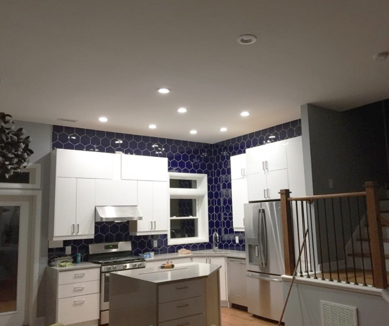 Kitchen remodel with blue tile and white cabinets